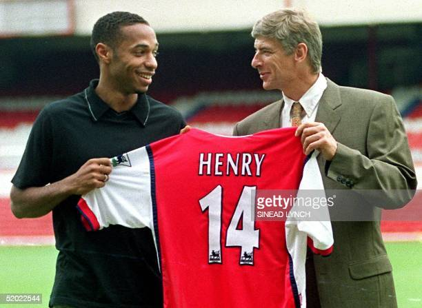 Striker Thierry Henry holds up his shirt with Manager Arsene Wenger having been signed for Arsenal 03 August 1999 from Juventus for an undisclosed...