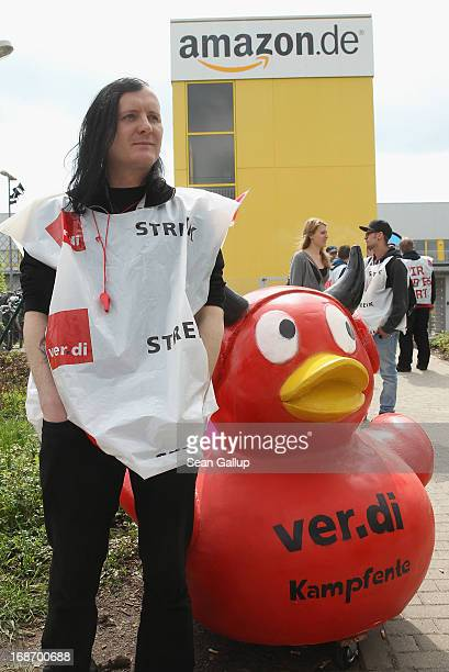 A striking Amazon worker waering a strike bib of the verdi service industry labour union stands next to the effigy of a devilish duck during a strike...
