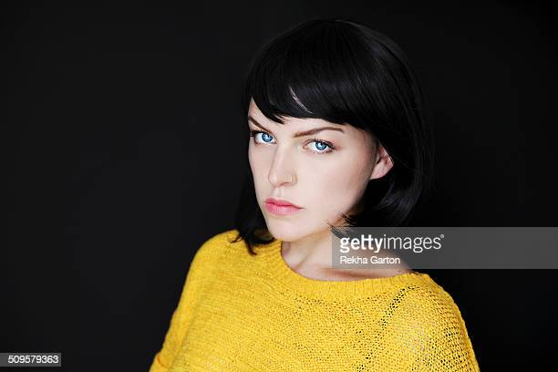 striking black haired woman on black background - rekha garton stock pictures, royalty-free photos & images