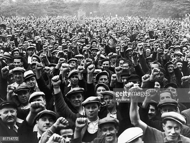 Striking building workers raise their fists in salute during a rally in the Bois de Vincennes, Paris, 13th June 1936.