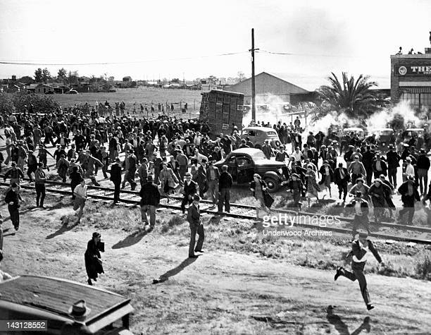 Striking cannery workers at odds with a truckload of spinach being taken into the newly reopened cannery, Stockton, California, April 23, 1937....