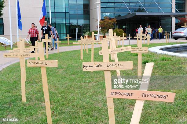 Striking employees of Nortel France, a subsidiary of the Canadian telecommunications firm Nortel, walk in front of fake crosses set up in front of...