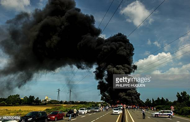 Striking employees of the My Ferry Link company block the access to the harbour after setting tyres on fire on July 31 2015 in Calais northern France...