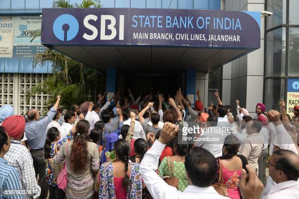 Striking Indian bank employees take part in a protest outside a branch of the State Bank of India in Jalandhar on August 22 2017 Bank employee unions...