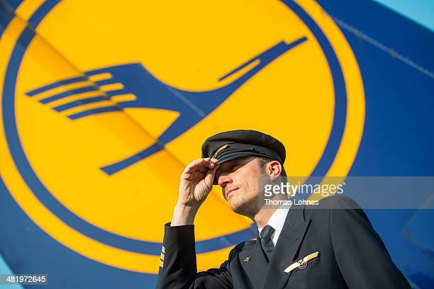 A striking Lufthansa pilot poses in front of the Lufthansa company logo at Frankfurt Airport on April 2 2014 in Frankfurt Germany The pilots who are...