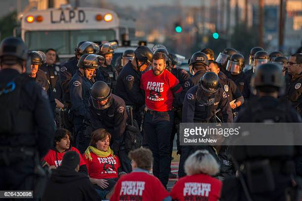 Striking McDonald's restaurant employees sitting in an intersection are arrested after walking off the job to demand a $15 per hour wage and union...