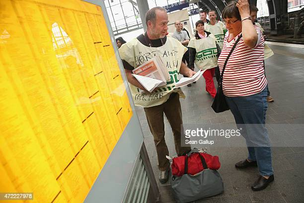 A striking member of the GDL train drivers' union distributes strike information leaflets during a stroll through Ostbahnhof train station on the...