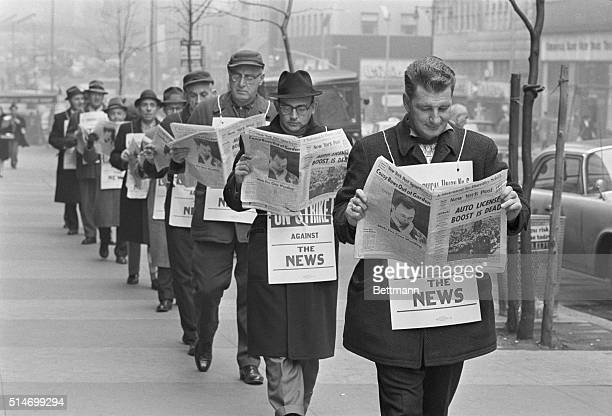 Striking members of the International Typographical Union read the New York Post as they picket The Post was the first of nine New York papers to...