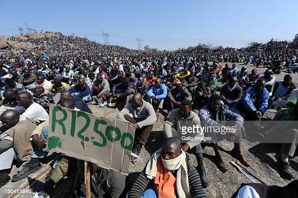 Striking mine workers demonstrate as they protest over wage demands outside the Nkageng informal settlement on August 16 2012 in North West South...