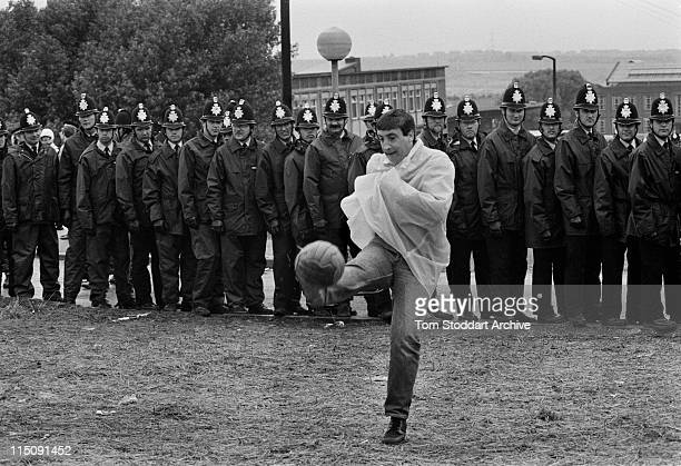 A striking miner plays football in front of police officers surrounding the British Steel Coking Plant in Orgreave South Yorkshire during the UK...