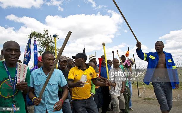 Striking miners chant slogans as they march to Wonderkop Stadium near Lonmin's platinum mine in Marikana on January 23 2014 Tens of thousands of...