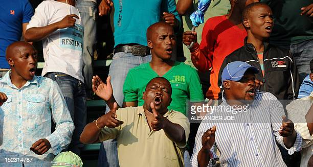 Striking miners gesture as they celebrate having secured a 22 percent pay hike from Londonlisted Lonmin platinum mine in Marikana on September 18...