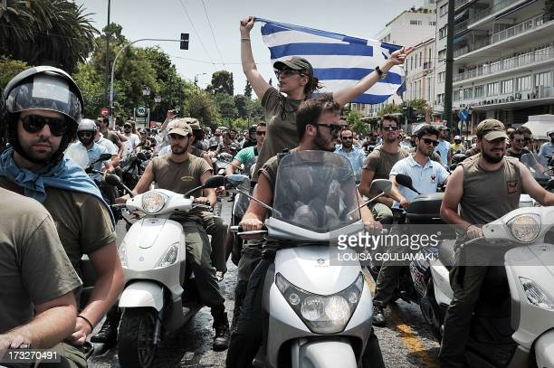 Striking municipal police display a Greek flag while driving their motorbikes by the Greek parliament in Athens during a protest on July 11 2013 The...