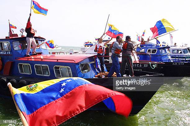 Striking oil workers hold Venezuelan flags as they head out on a boats to show their support for crewmembers on strike on oil tankers December 6 2002...