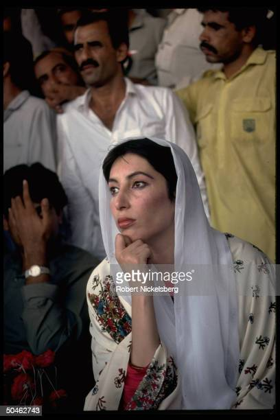 Striking pose of Pakistani leader Benazir Bhutto sitting among group of supporters during election campaign