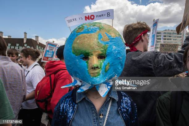 A striking school student with a planet mask on Westminster bridge on June 21 2019 in London England School students walk out of their classes to...