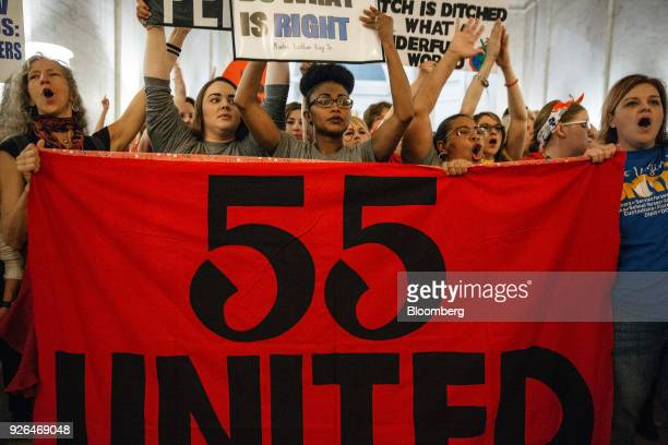"Striking school workers hold a ""55 United"" sign while chanting inside the West Virginia Capitol in Charleston, West Virginia, U.S., on Friday, March..."