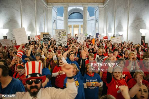 Striking school workers hold signs and chant inside the West Virginia Capitol in Charleston, West Virginia, U.S., on Friday, March 2, 2018. A week...