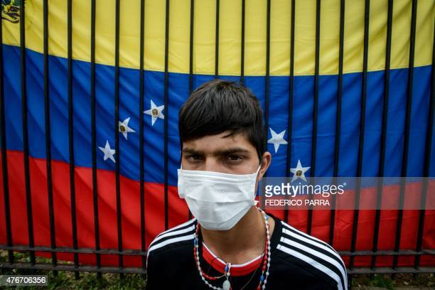 A striking university student poses in front of a Venezuelan national flag during the 15th day of a hunger strike demanding the government of...