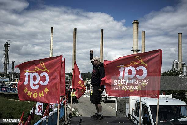 A striking worker stands next to French CGT union flags in front of the Total oil refinery of Feyzin near Lyon centraleastern France on May 24 during...