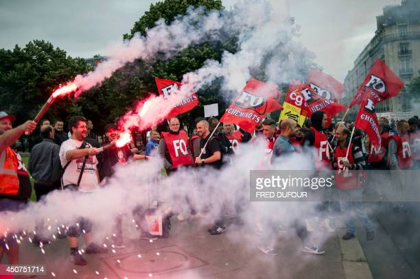 Striking workers of the French staterun rail operator SNCF backed by French unions CGT and SudRail light flares as they demonstrate against reform...