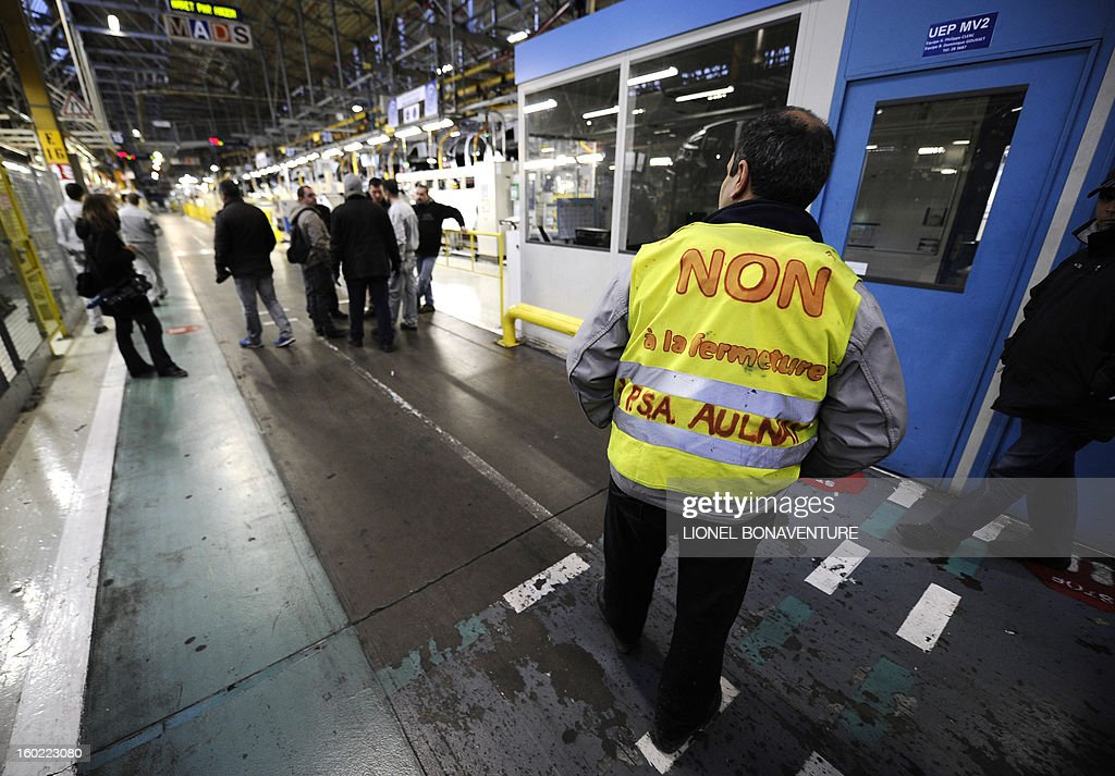 Striking workers of the PSA Peugeot Citroen carmaker plant of Aulnay-sous-Bois, a Paris' suburb, gather on January 28, 2013 at the plant, during a general assembly. The striking workers occupy the factory to protest against plans to sell the plant and lay off thousands of employees.