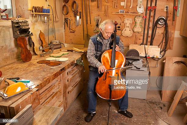 string instrument maker playing a cello he made. - instrument maker stock photos and pictures