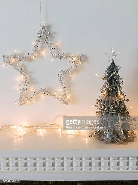 string lights with christmas trees and star decor on mantelpiece at home - stars and strings stock photos and pictures