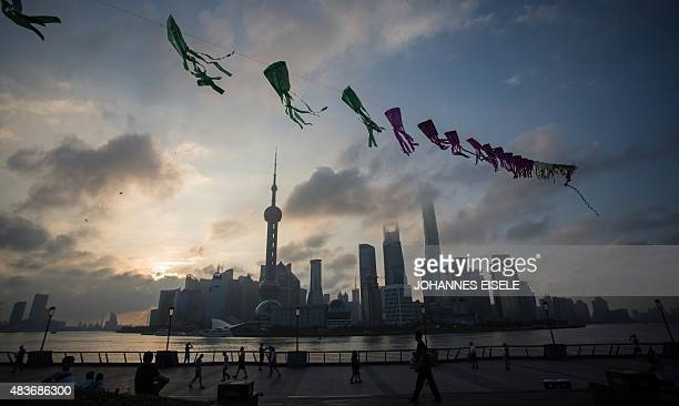 A string of kites fly during sunrise as pedestrians walk on the Bund in front of the financial district of Pudong in Shanghai on August 12 2015 AFP...