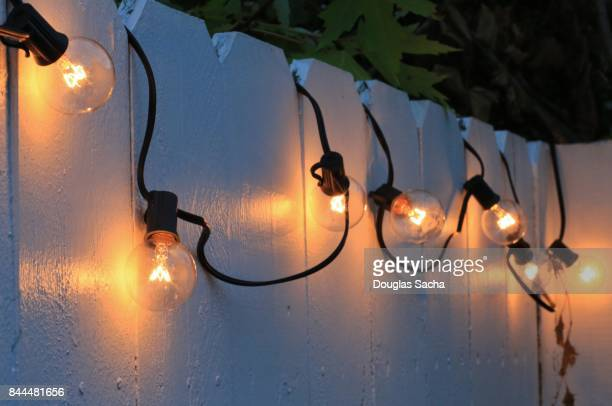 String of patio lights on a white fence