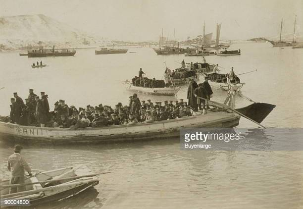 String of pontoons in tow of stream launch approaching landing stage with load of Japanese infantry troops