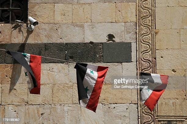 String of three Syrian national flags watched over by a surveillance camera mounted on a bullet damaged wall in the old town of Damascus, Syria.