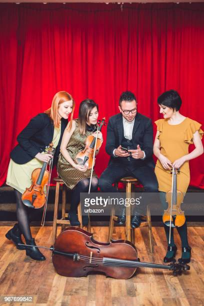 string quartet after the concert  on stage looking in mobile phone. - string quartet stock photos and pictures