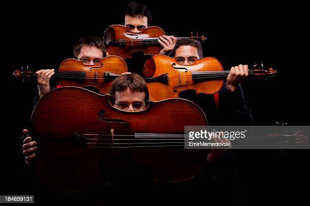 a string quartet on a dark background - musical quartet stock photos and pictures