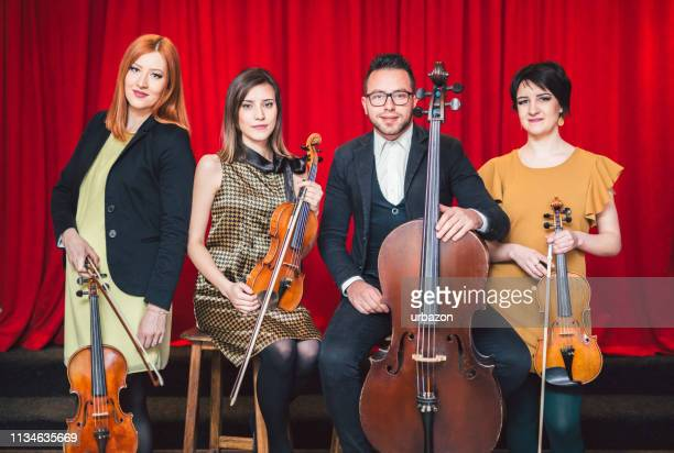 string quartet posing after the concert on stage. - string quartet stock photos and pictures