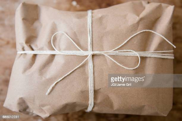 String tied around package wrapped in brown paper