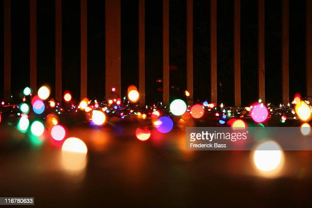 Strings of illuminated Christmas lights laying on a balcony, outdoors