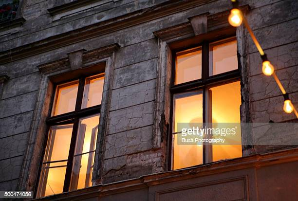 Strings of light bulbs in front of facade of old building in Berlin