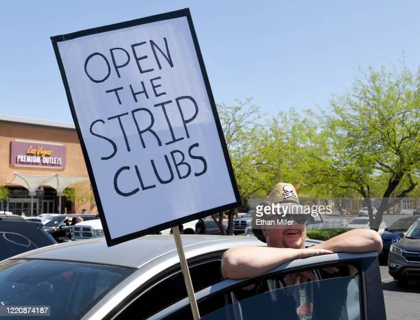 Strip club DJ Jack Slammy of Nevada displays a sign as people gather for a protest caravan along the Las Vegas Strip hosted by conservative radio...
