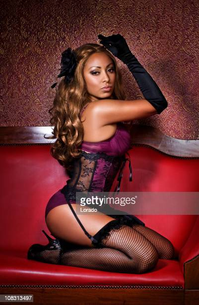strip girl  sitting on sofa - garter belts and stockings stock photos and pictures
