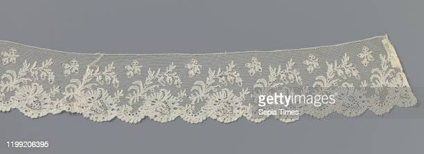 Strip of bobbin lace with an obliquely placed flower under a branched branch, Strip of natural-colored bobbin lace: Lille lace. The repeating pattern...
