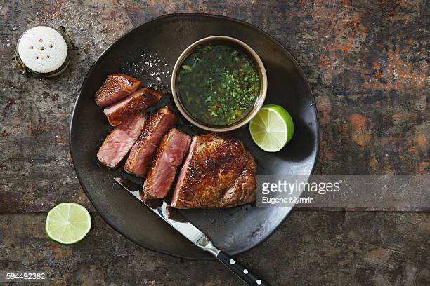 strip steak with chimichurri sauce - beef stock pictures, royalty-free photos & images