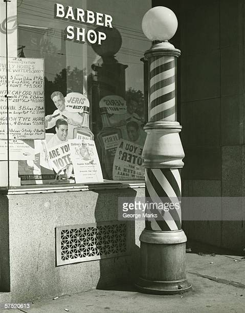 striped barber pole outside shop, (b&w) - barber pole stock photos and pictures