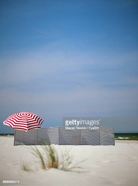 Striped Canvas And Umbrella At Beach Against Sky On Sunny Day