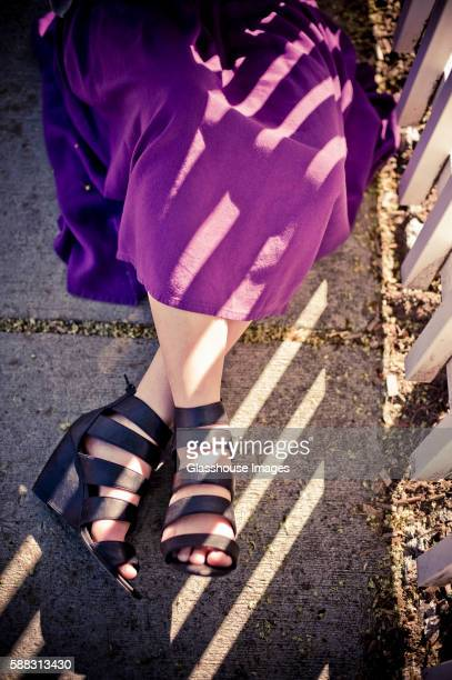 Striped Shadows Across High-Heel Shoes and Purple Skirt