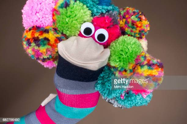 striped sock puppet with pom-pom hair and goodly eyes - puppet stock pictures, royalty-free photos & images