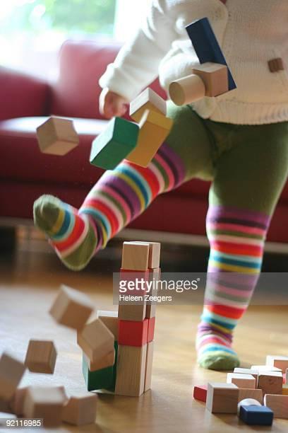 Striped tights toddler leg kicking tower of blocks