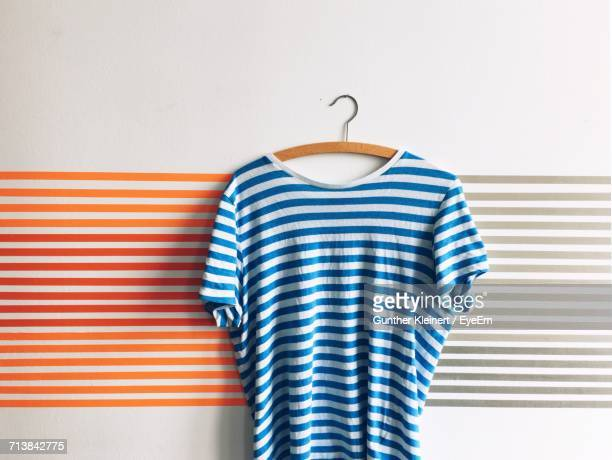 Striped T-Shirt Hanging On Coathanger Against Patterned Wall