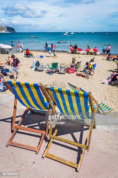 Stripey seaside deckchairs beside a crowded sandy beach holidaymakers sunbathers