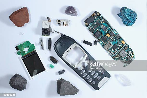 A stripped down mobile phone and mobile phone parts lie on a table with minerals representing substances typically found in a mobile phone including...